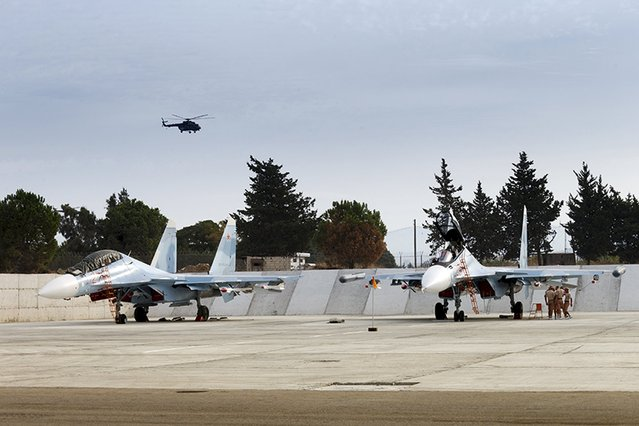 Sukhoi Su-30 fighter jets are seen on the tarmac at the Hmeymim air base near Latakia, Syria, in this handout photograph released by Russia's Defence Ministry on October 22, 2015. (Photo by Reuters/Ministry of Defence of the Russian Federation)