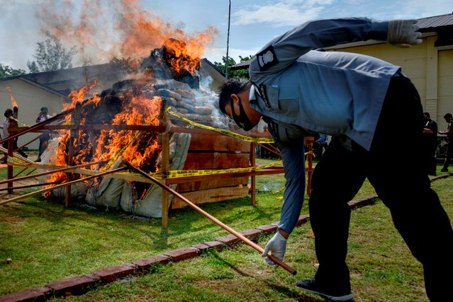 Indonesian narcotic policemen burn a pile of confiscated marijuana during a ceremony at the regional police headquarters in Banda Aceh on September 23, 2020. Some 372.6 kilograms of marijuana, 80.2 kilograms of methamphetamines, and 27,400 ecstacy pills that were previously seized by police were destroyed during the event. (Photo by Chaideer Mahyuddin/AFP Photo)