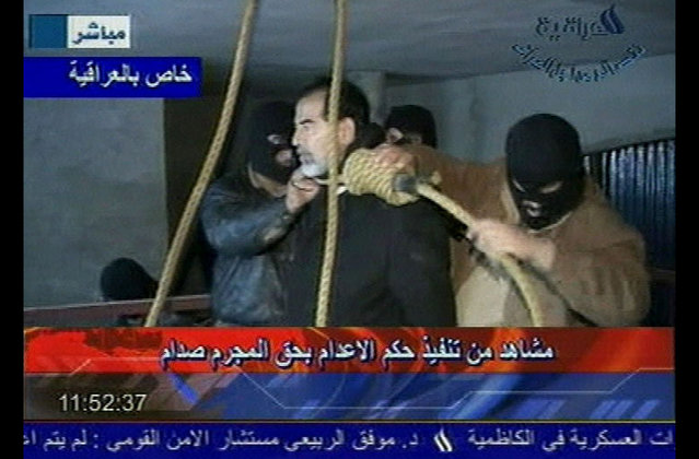 This video image released by Iraqi state television shows Saddam Hussein's guards wearing ski masks and placing a noose around the deposed leader's neck moments before his execution, on December 30. 2006. Clutching a Quran and refusing a hood, Saddam Hussein went to the gallows before sunrise, executed by vengeful countrymen after a quarter-century of remorseless brutality that killed countless thousands and led Iraq into disastrous wars against the United States and Iran. (Photo by AP Photo/IRAQI TV/The Atlantic)