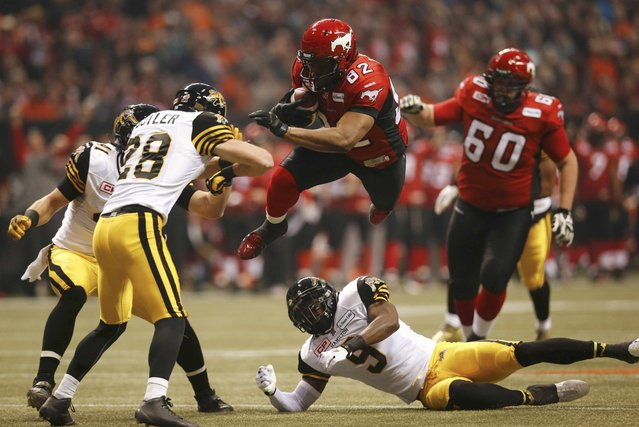 Calgary Stampeders' Nike Lewis (82) jumps over Hamilton Tiger Cats' Brandon Stewart (9) while running the football in the first half during the CFL's 102nd Grey Cup football championship in Vancouver, British Columbia, November 30, 2014. (Photo by Mark Blinch/Reuters)
