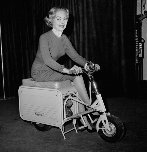 Joan Kagman demonstrates a new portable scooter designed for compact transport in a car, plane or boat or for storing in an apartment. It was shown at the International Sports, boat and vacation show in Chicago, on January 23, 1961. The scooter, equipped with a one cylinder motor and seating two, can, according to its makers, ranch a top speed of 35 miles on hour and can go as far as 165 miles on a gallon of gasoline. It weighs but 84 pounds. (Photo by AP Photo/ESK)