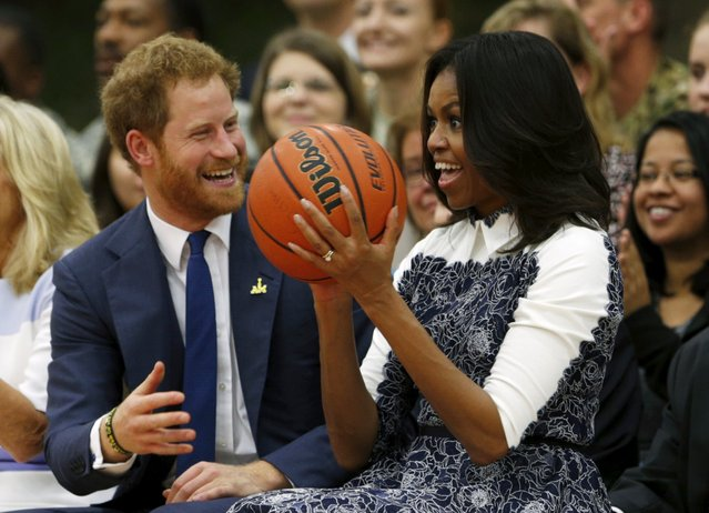 Britain's Prince Harry laughs as U.S. first lady Michelle Obama catches a basketball during a game played by wounded warriors at Fort Belvoir, Virginia October 28, 2015. Prince Harry is at Fort Belvoir to meet soldiers and spread the word about the Invictus Games, which supports wounded warriors. Prince Harry spearheaded the Invictus Games, which was first held in London last September. The next Invictus Games is planned for May in Orlando, Florida. (Photo by Kevin Lamarque/Reuters)