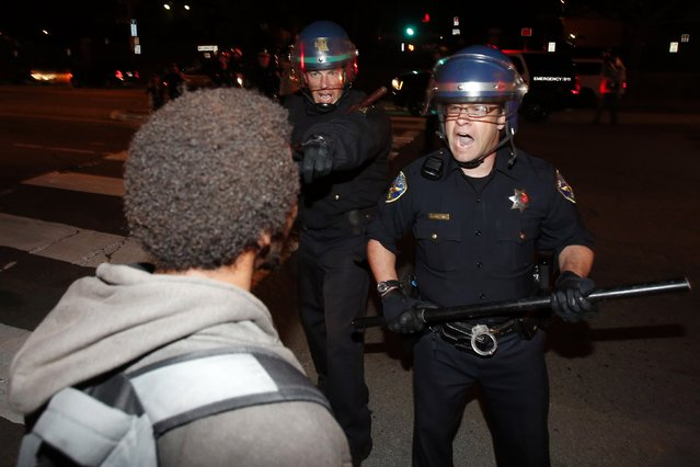 Police officers confront a demonstrator during a demonstration against the grand jury decision in the Ferguson, Missouri shooting of Michael Brown near the San Francisco General Hospital in San Francisco, California November 28, 2014. (Photo by Stephen Lam/Reuters)