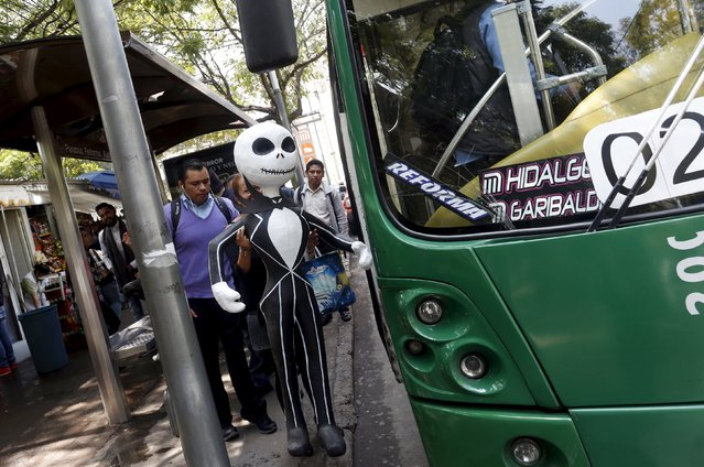 A woman holds a pinata of a fictional film character as she gets on the bus in Mexico City October 29, 2015. (Photo by Carlos Jasso/Reuters)