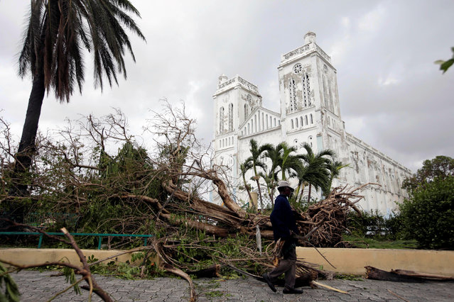 A man carrying branches from fallen trees walks next to the Cathedral after Hurricane Matthew in Les Cayes, Haiti, October 5, 2016. (Photo by Andres Martinez Casares/Reuters)