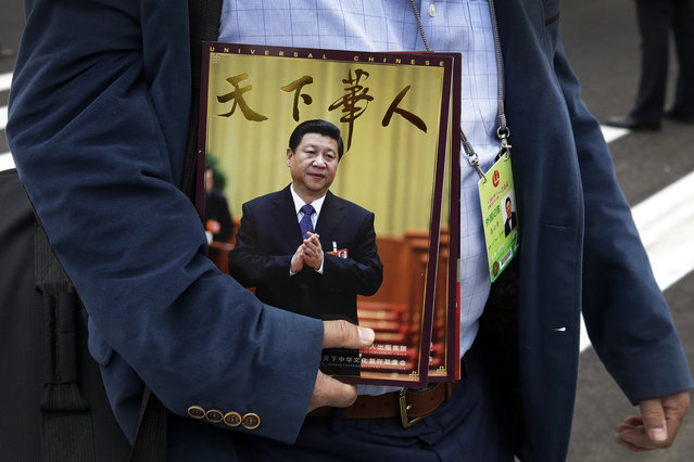 In this Saturday, March 3, 2018, photo, a journalist carrying magazines featuring Chinese President Xi Jinping on their front cover arrives for the opening of the Chinese People's Political Consultative Conference (CPPCC) at the Great Hall of the People in Beijing. Xi, poised to rule over China indefinitely, is at the center of the Communist Party's most colorful efforts to build a cult of personality since the death of the founder of the People's Republic, Mao Zedong, in 1976. (Photo by Andy Wong/AP Photo)