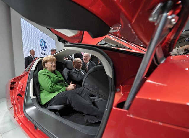 German Chancellor Angela Merkel, left, and Russian President Vladimir Putin, right, visit the Hannover Fair, in Hannover, central Germany, on Monday, April 8, 2013. (Photo by Alexei Druzhinin/AP Photo/RIA Novosti/Presidential Press Service)