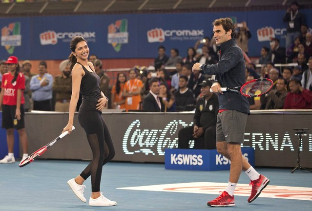 Bollywood actress Deepika Padukone, left, shares a lighter moment with Roger Federer during a fun match in the sidelines of the International Premier Tennis League, in New Delhi, India, Monday, December 8, 2014. (Photo by Manish Swarup/AP Photo)