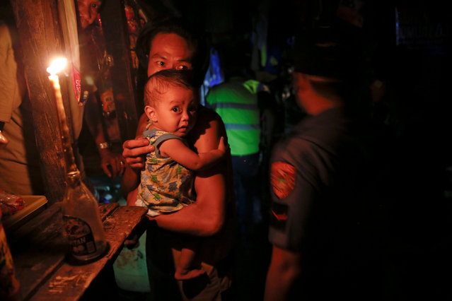 A man holds a baby as police searches a slum during a drug raid, in Manila, Philippines, October 7, 2016. (Photo by Damir Sagolj/Reuters)