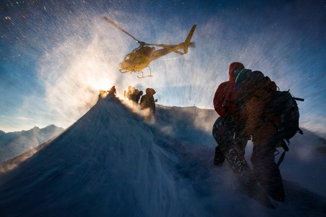 Technical staff take shelter as a helicopter takes off prior to the Nendaz Freeride skiing and snowboard competition, a Freeride World Tour Qualifier (FWQ) event, on the Mont Gond in Nendaz, Switzerland on March 21, 2018. (Photo by Valentin Flauraud/EPA/EFE/Rex Features/Shutterstock)