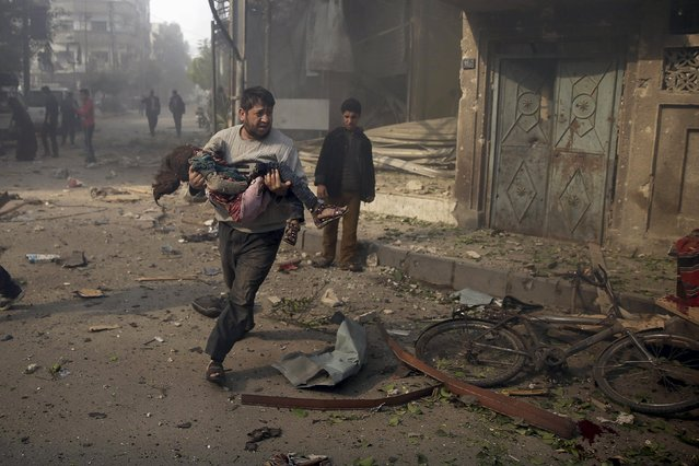 A man carries an injured girl as he rushes away from a site hit by what activists said were airstrikes by forces loyal to Syria's President Bashar al-Assad, in the Douma neighborhood of Damascus, Syria November 7, 2015. (Photo by Bassam Khabieh/Reuters)