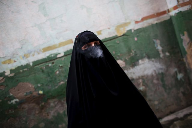 Gisele Marie, a Muslim woman and professional heavy metal musician, smokes a cigarette before a fund raising concert for Syrian refugges in Brazil, in Rio de Janeiro November 8, 2015. (Photo by Nacho Doce/Reuters)