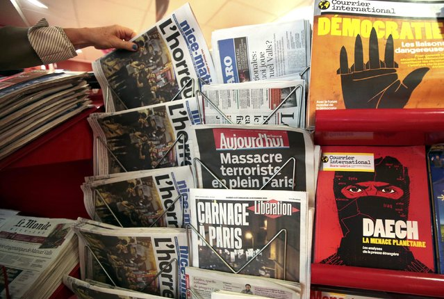 "A woman takes the local newspaper at a news stand which displays a magazine (R bottom) which reads ""Daech, the planetary threat"" in NIce, France, November 14, 2015, the day after fatal shootings in the French capital. (Photo by Eric Gaillard/Reuters)"