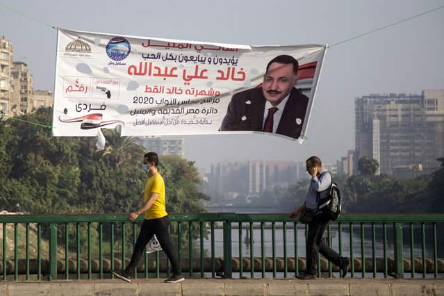 Men walk under election campaign banners ahead of parliamentary elections, in Cairo, Egypt, 23 October 2020. Parliamentary elections are scheduled to be held in Egypt on 24 and 25 October 2020, and on 07 and 08 November 2020 to elect the House of Representatives. (Photo by Mohamed Hossam/EPA/EFE)