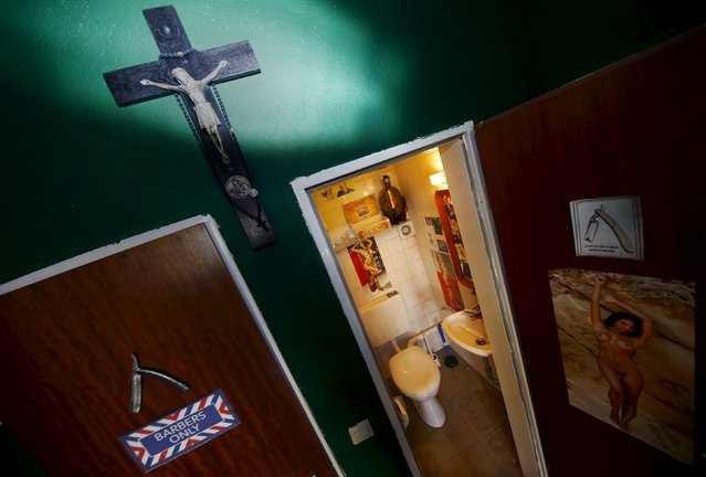 """A cross hangs outside the toilet in Torreto Barbershop in Frankfurt, Germany, October 13, 2015. The toilet is used by the visitors and shop owner, Alex """"Torreto"""" Velios who lives and works at his shop in Frankfurt. (Photo by Kai Pfaffenbach/Reuters)"""