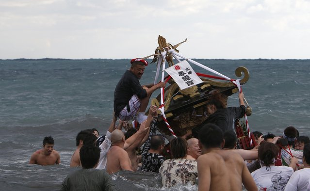 "Man balances as he rides on a ""mikoshi"" or portable shrine as local people carry it into the sea during a festival to wish for calm waters in the ocean and good fortune in the new year in Oiso, west of Tokyo, January 1, 2015. (Photo by Yuya Shino/Reuters)"