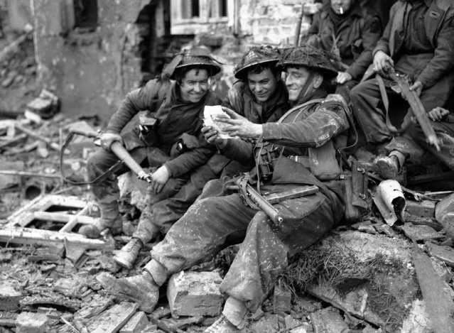 Happiness registers on the faces of these British soldiers as they read their first mail on German soil, amid the ruins of a German village, on the road to the Rhine on February 15, 1945. From left to right; Private J. Laird, from Scotland, Private J. Bryce, from Scotalnd and Corporal D. Devine from England. (Photo by AP Photo)