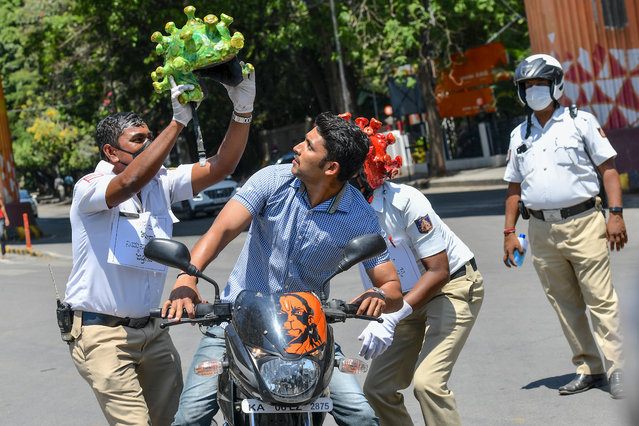 Traffic police personnel (L and R) wearing coronavirus-themed helmets perform in front of a motorist (C) as they participate in a campaign to educate the public during a government-imposed nationwide lockdown as a preventive measure against the COVID-19 coronavirus in Bangalore on March 31, 2020. (Photo by Manjunath Kiran/AFP Photo)