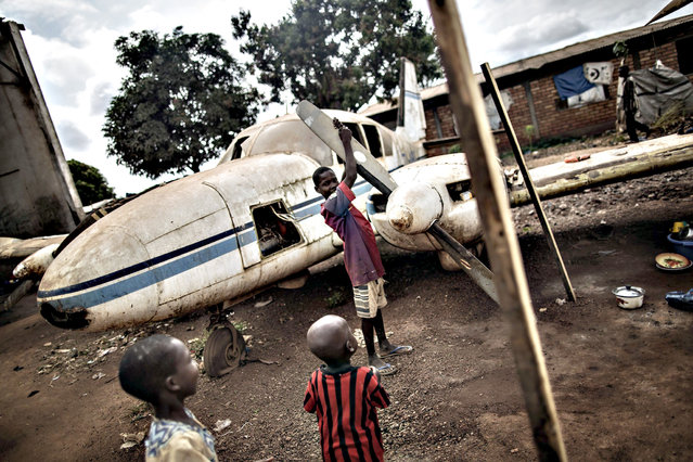 """Children play with the wreckage of a light plane at the Mpoko Internally Displaced People (IDP) camp in Bangui on November 26, 2015, ahead of a historical visit by the pope. Pope Francis held his first open-air mass in Africa on November 26 with huge crowds calling heavy rains """"God's blessing"""" as they sung and danced in the Kenyan capital. The 78-year-old pontiff, the third pope to visit the continent, is also scheduled to visit Uganda and the troubled Central African Republic (CAR) on a six-day trip. (Photo by Gianluigi Guercia/AFP Photo)"""