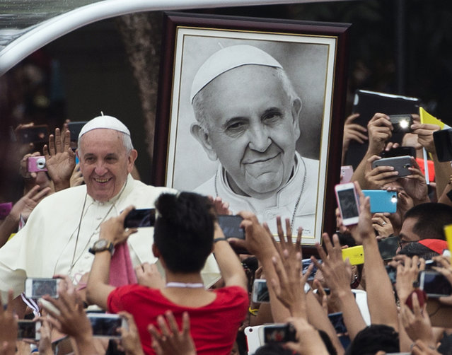 Pope Francis passes past a portrait of himself as he arrives to meet youths in Santo Tomas University in Manila, Philippines, Sunday, January 18, 2015. Francis is in the Philippines on Sunday, the final full day of a weeklong trip that also took him to Sri Lanka. (Photo by Alessandra Tarantino/AP Photo)