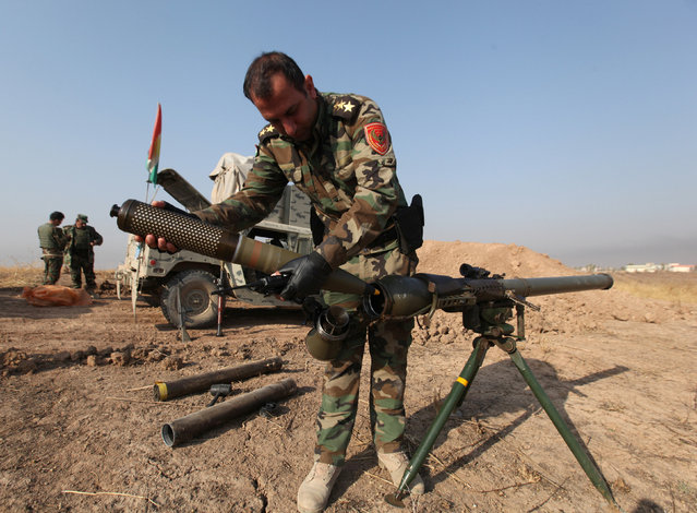 A member of the Peshmerga forces inspects a weapon near the town of Bashiqa, east of Mosul, during an operation to attack Islamic State militants in Mosul, Iraq, November 7, 2016. (Photo by Azad Lashkari/Reuters)