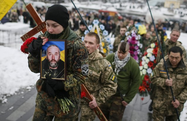 "Bogdanna Nikonenko holds a portrait of her father Sergiy as she takes part in a funeral ceremony for the serviceman from the battalion ""Aydar"", who was killed in the fighting in Luhansk region in eastern Ukraine, at the Independence Square in central Kiev, January 20, 2015. (Photo by Gleb Garanich/Reuters)"