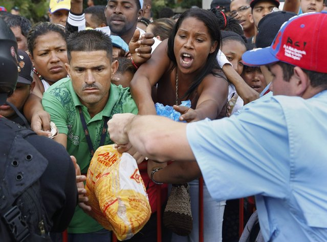 People crowd together in an attempt to buy chickens at a Mega-Mercal, a subsidized state-run street market, in Caracas January 24, 2015. President Nicolas Maduro shook up complex currency controls on Wednesday and also prepared Venezuelans for a rise in the world's cheapest fuel prices in response to a recession worsened by plunging oil revenue. (Photo by Carlos Garcia Rawlins/Reuters)