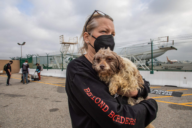 "A volunteer holds a rescued dog after 29 dogs arrived at Los Angeles International Airport on February 13, 2021. The dogs were rescued from the Yulin Dog Meat Festival in China and Chinese dog meat markets by ""No Dogs Left Behind"", a global animal welfare organization. The dogs are on their way to forever homes in New York. (Photo by Apu Gomes/AFP Photo)"