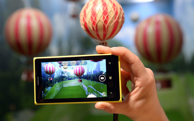 A employee demonstrates the photo capabilities of the Nokia Lumia 1020, a Windows Phone with a 41-megapixel camera, after its unveiling in New York on July 11, 2013. (Photo by Timothy Clary/AFP Photo)