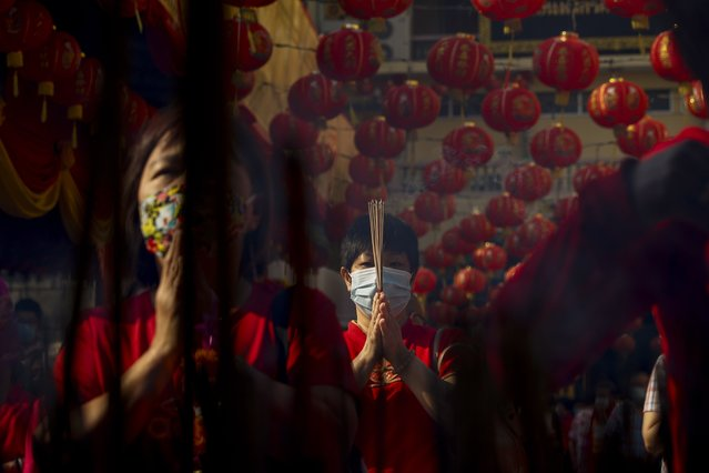 People wearing protective face masks burn incense for good fortune at a Chinese temple during celebrations for the Lunar New Year in Bangkok, Thailand, 12 February 2021. The Lunar New Year, also known as Spring Festival in China and Tet in Vietnam, falls on 12 February this year, marking the start of the Year of the Ox, one of the 12 animals of the Chinese Zodiac. (Photo by Diego Azubel/EPA/EFE)