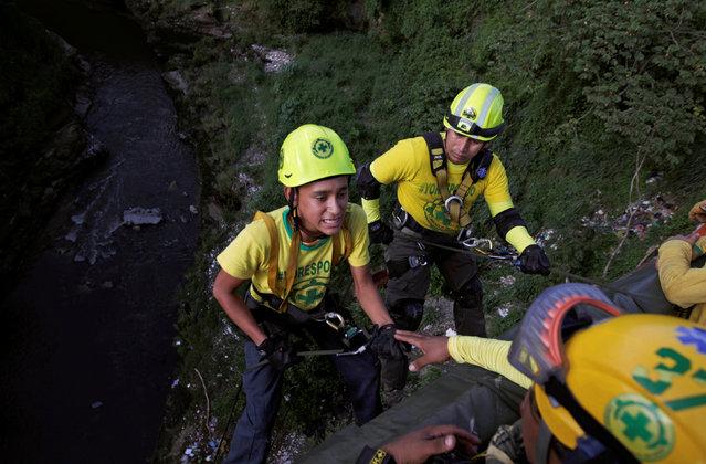 Volunteer Carlos Rodas (L) prepares for his first jump with rescuer Josue Najarro as they participate in a vertical rescue practice in San Salvador, El Salvador July 13, 2016. (Photo by Jose Cabezas/Reuters)