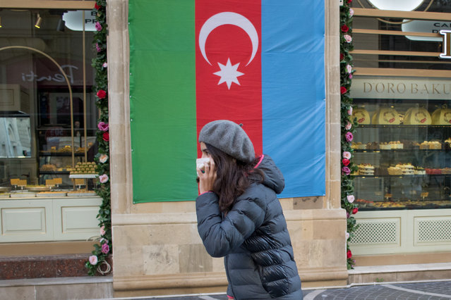 Citizens walk in front of the Azerbaijan flag on December 14, 2020 in Baku, Azerbaijan. The country's cafes and restaurants are closed through Jan 18th, and all stores besides grocers and pharmacies will be limited to delivery. Travel is restricted between cities, and an SMS-based permission system was reimposed, whereby people need to request permission to run essential errands. Azerbaijan hopes the measures will curb a spike in covid-19 cases that started in October. (Photo by Aziz Karimov/Getty Images)