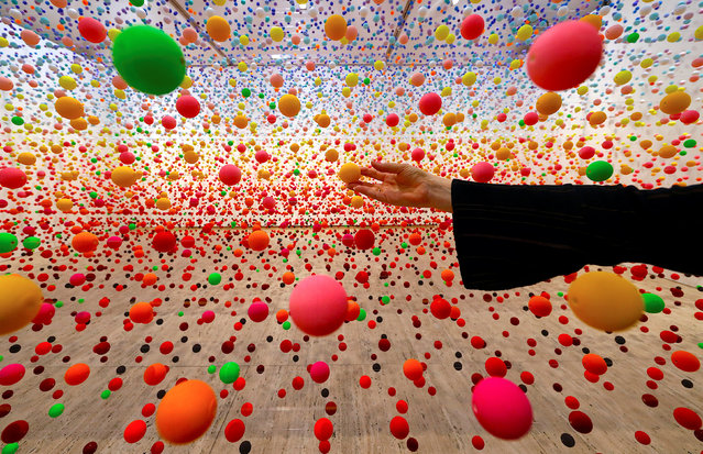 """Australian artist Nike Savvas adjusts her installation artwork piece, consisiting of over 50,000 polystyrene balls, titled """"Atomic: full of love full of wonder"""" as it is installed for the upcoming exhibition """"Spacemakers and roomshakers: installations from the collection"""" at the New South Wales Art Gallery in Sydney, Australia, July 12, 2018. (Photo by David Gray/Reuters)"""