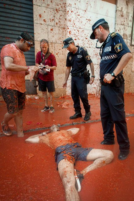 """A reveller lies in tomato pulp as police stand above during the annual """"Tomatina"""" festivities in the village of Bunol, near Valencia on August 31, 2016. Today at the annual Tomatina fiesta 160 tonnes of ripe tomatoes were offloaded from trucks into a crowd of 22,000 half-naked revellers who packed the streets of Bunol for an hour-long battle. (Photo by Biel Alino/AFP Photo)"""