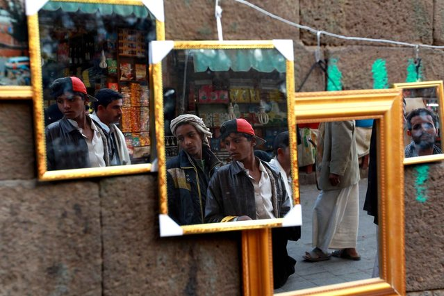 Mirrors displayed at a market show the reflections of young Yemenis in Sanaa's old city on January 22, 2015. Shiite militiamen maintained a tight grip on Yemen's capital with fighters deployed around the presidential palace despite a deal to end what authorities called a coup attempt. (Photo by Mohammed Huwais/AFP Photo)