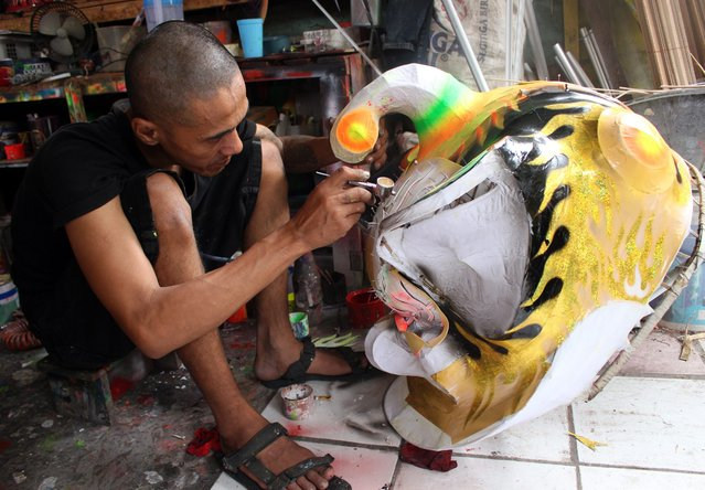 An Indonesian worker paints a dragon mask for the upcoming Lunar New Year at a traditional Chinese dragon and lion masks and custome maker in Bogor, Indonesia, 02 February 2015. (Photo by Adi Weda/EPA)