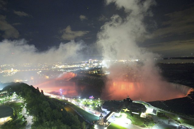 An overall view shows the American Falls (L) and the Horseshoe Falls (R) lit by lights in Niagara Falls, Ontario, Canada, August 21, 2015. Picture taken August 21, 2015. (Photo by Charles Platiau/Reuters)