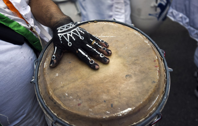 """A musician rests his hand on a drum while performing at the """"Las Llamadas"""" parade during Carnival celebrations in Montevideo, Uruguay, Friday, February 6, 2015. (Photo by Matilde Campodonico/AP Photo)"""