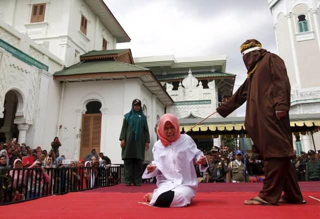 Nur Elita, an Acehnese woman, screams during caning as part of her sentence in the courtyard of Baiturrahman mosque in Banda Aceh, Indonesia's Aceh province December 28, 2015. Nur Elita  received five strokes of the cane for having pre-marital s*x with her boyfriend, according to local media. Aceh is the only province in Indonesia, the world's most populous Muslim country, where Islamic law is implemented, according to local media. (Photo by Junaidi Hanafiah/Reuters)