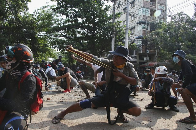 Anti-coup protesters use sling shot to confront police at Thaketa Township in Yangon, Myanmar, Sunday, March 28, 2021. (Photo by AP Photo/Stringer)