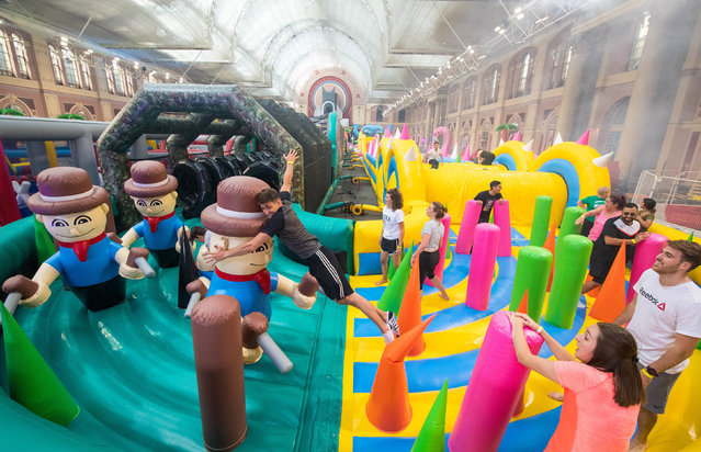 People tackle The Monster, a 300 metre long inflatable obstacle course for adults, at Alexandra Palace, London, UK on Friday, August 24, 2018. (Photo by Dominic Lipinski/PA Wire)