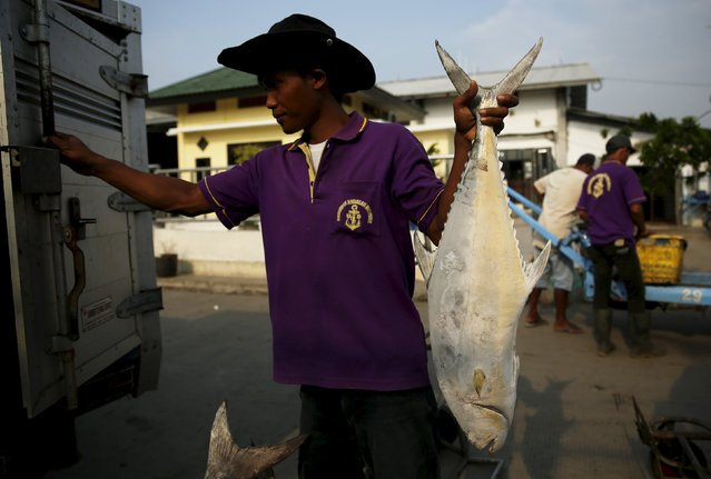 A worker carries a frozen fish to sell at Muara Angke fish auction in Jakarta, January 4, 2016. (Photo by Reuters/Beawiharta)