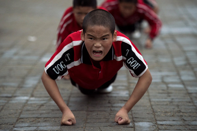 "This picture taken on October 20, 2016 shows students practising wushu at the Tagou martial arts school in Dengfeng. China is investing hugely in football training and has vowed to have 50 million school- age players by 2020, as the ruling Communist party eyes ""football superpower"" status by 2050. Some 1,500 students from the vast Tagou martial arts school, a few miles from the cradle of Chinese kungfu, the Shaolin Temple in Henan province, have signed up for its new soccer programme, centred on a pristine green Astroturf football pitch where dozens of children play simultaneous five- a- side- games. (Photo by Nicolas Asfouri/AFP Photo)"
