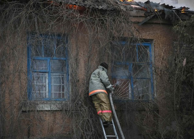A firefighter extinguishes a building after shelling in Artemivsk, estern Ukraine February 14, 2015. (Photo by Gleb Garanich/Reuters)