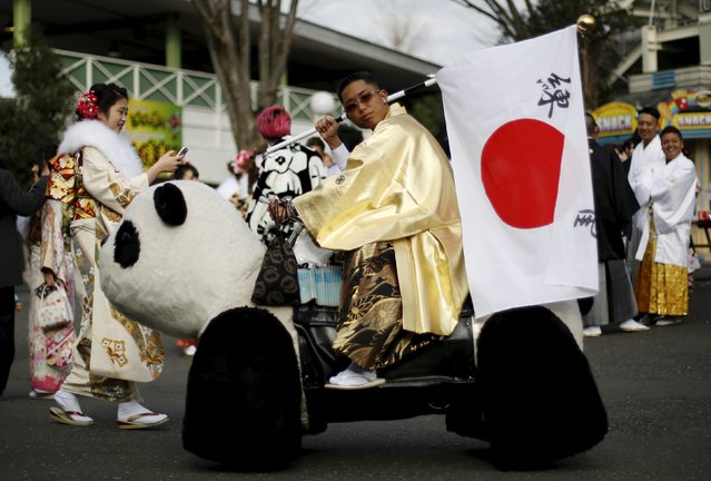 A Japanese man wearing kimonos and holding a Japanese national flag rides on a panda-shaped vehicle after his Coming of Age Day celebration ceremony at an amusement park in Tokyo January 11, 2016. (Photo by Yuya Shino/Reuters)