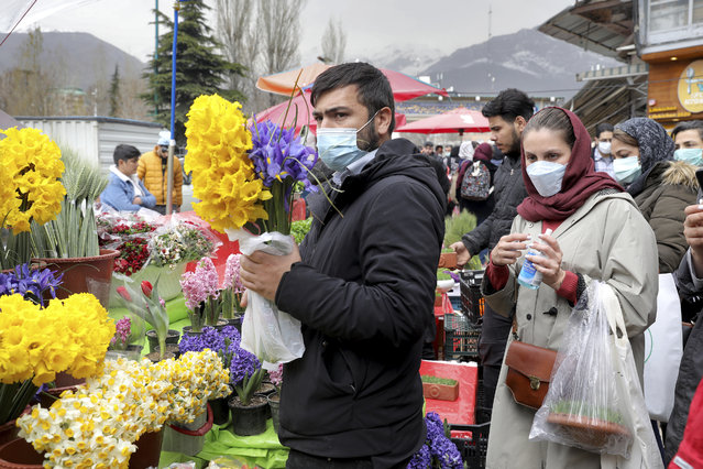 """Customers buy flowers to celebrate the Persian New Year, or Nowruz, meaning """"New Day"""" in northern Tajrish Square, Tehran, Iran, Wednesday, March 17, 2021. (Photo by Ebrahim Noroozi/AP Photo)"""