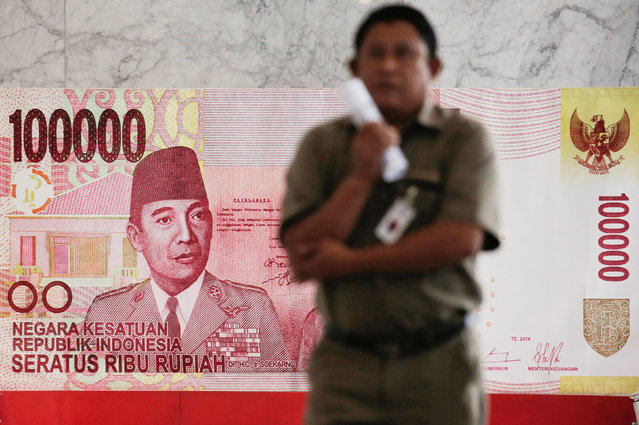 A man walks past a poster of a one hundred thousand Rupiah banknote inside Indonesia's central bank, Bank Indonesia, in Jakarta, November 17, 2016. (Photo by Reuters/Beawiharta)