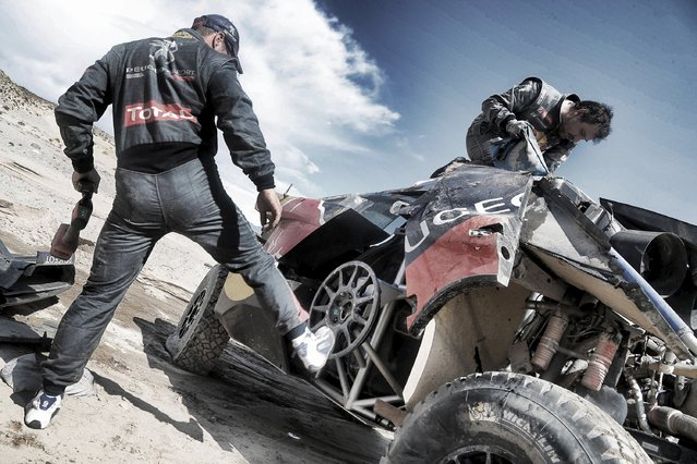 Sebastien Loeb (L) of France and co-pilot Daniel Elena work on his car after he had an accident which turned the car over during the eighth stage of the Dakar Rally 2016 near Belen, Argentina, January 11, 2016. (Photo by Andre Lavadinho/Reuters)