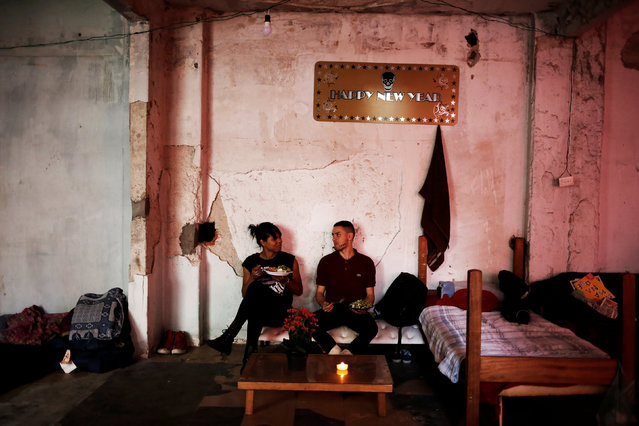 Fernanda (L), 20, and Aleksander, 23, who are among members of lesbian, gay, bisexual and transgender (LGBT) community, that have been invited to live in a building that the roofless movement has occupied, sit on a makeshift sofa, in downtown Sao Paulo, Brazil, November 16, 2016. (Photo by Nacho Doce/Reuters)