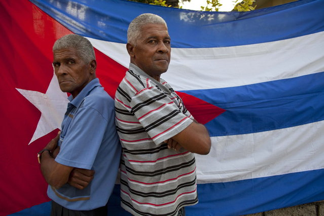In this September 29, 2013 photo, twins Orlando Gonzalez, left, and Roberto Gonzalez pose for a portrait in front a Cuban flag along their street in Havana, Cuba. The Gonzalez brothers are one of 12 sets of twins living along two consecutive blocks in western Havana, ranging in age from newborns to senior citizens. (Photo by Ramon Espinosa/AP Photo)